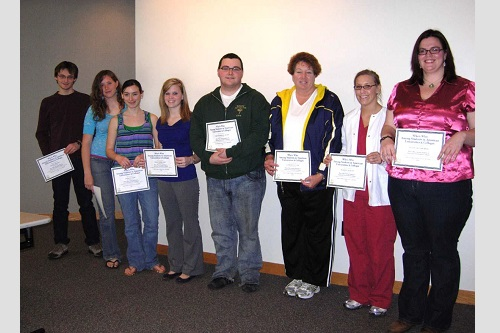 Who's Who award winners standing with certificates.