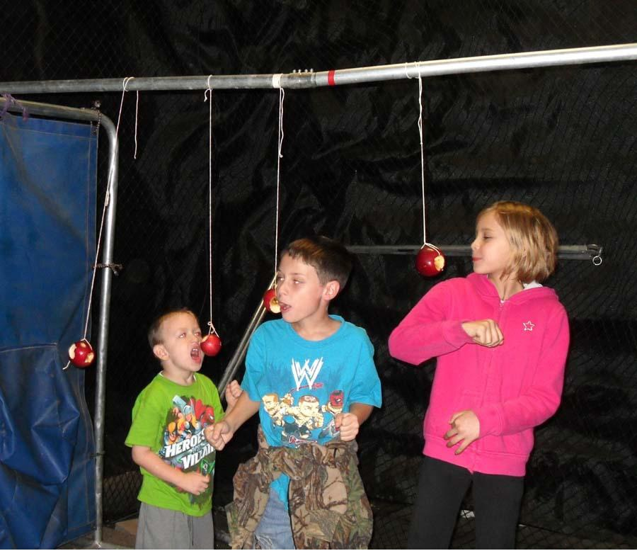 Haunted Forest kids eating apples on a string game.