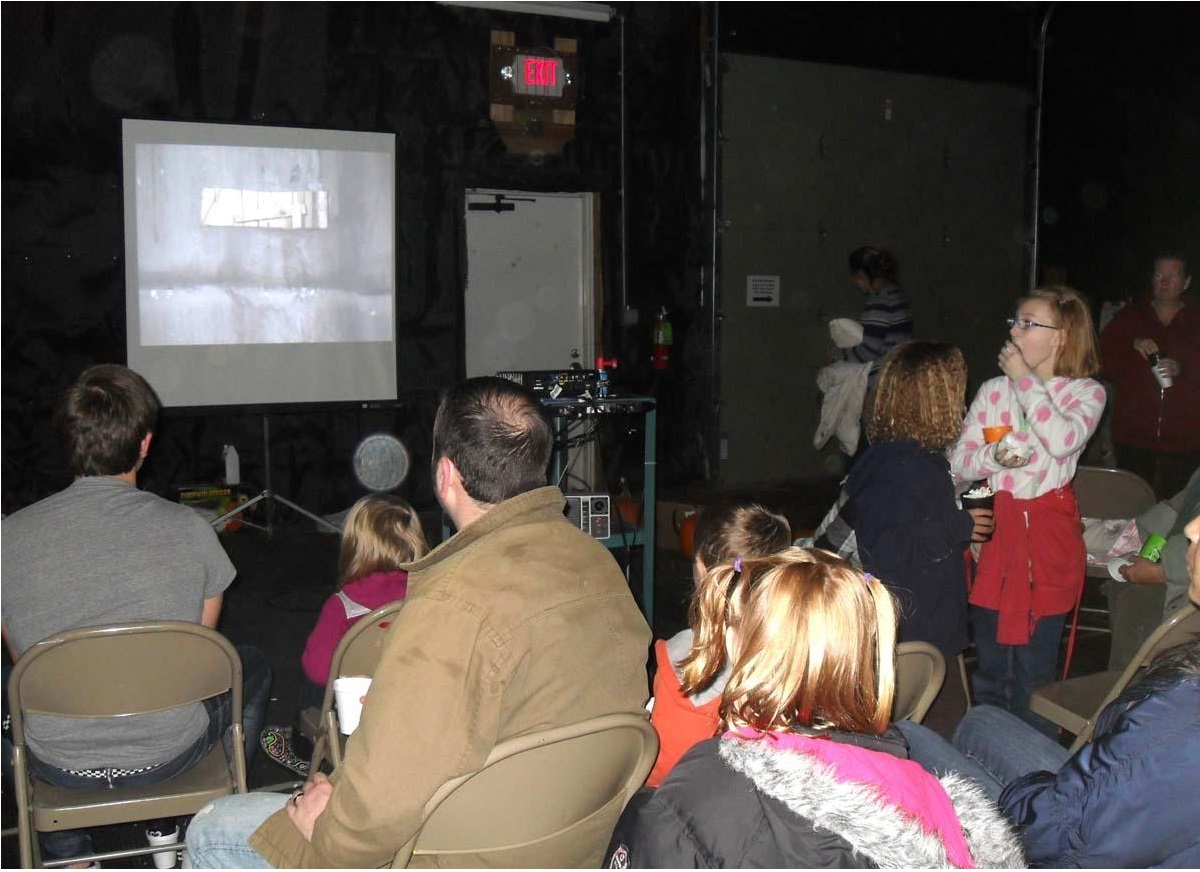 Haunted forest guests looking on to projector.