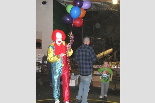 Haunted Forest clown, Dr. Lester Keith, with balloons and event goers getting snacks.