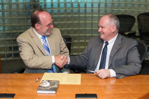 From left, Ferris State University Provost and Vice-president Fritz Erickson and Glen Oaks Community College President Dr. Gary Wheeler sign a reverse transfer agreement at Ferris in Big Rapids, Mich.