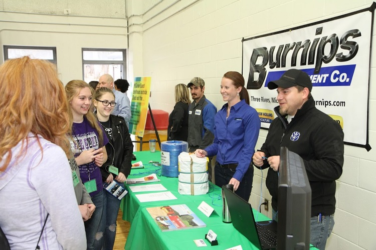 Students learn about jobs in agriculture from employees of Burnips Equipment.