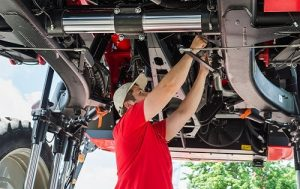 Auto mechanic working underneath a lifted