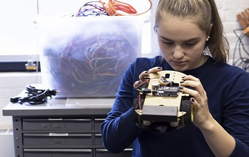 STEM student working in a small electronics lab, looking through inventory for her electronics project.