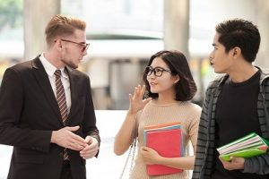 Businessman and college students discussing education on outdoor background