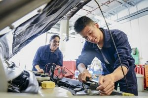 Two trainee car mechanics in garage repairing car, young man smiling and concentrating
