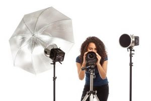 Subject: A woman photographer in action with her camera and lighting equipment, a small business photography studio.