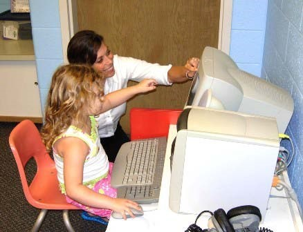 Michelle Johnson helping student on computer.