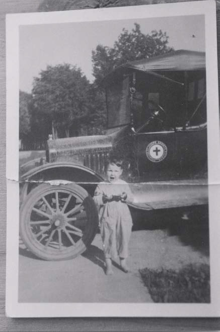 An 1919 photo of a boy in front of an amulance.