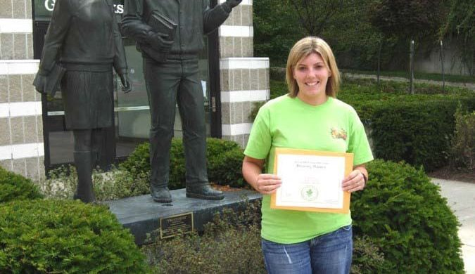"""Brandi Fisher showing off her """"tuition-free Glen Oaks Community College academic class"""" award."""
