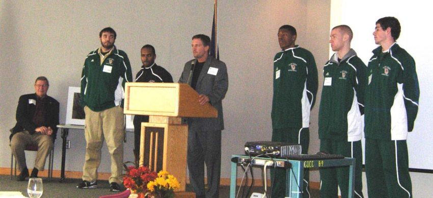 Steve Proefrock standing at podium with other coaches.