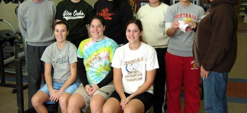 Members of softball team posing in weight room for photo.