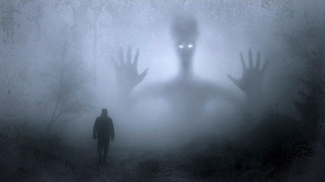 Man walking in fog with large alien shadow waiting.