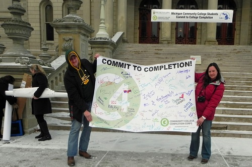 Anne McLeod and Eric Connelly showcasing a banner in Lansing where students pledged to complete their degrees.