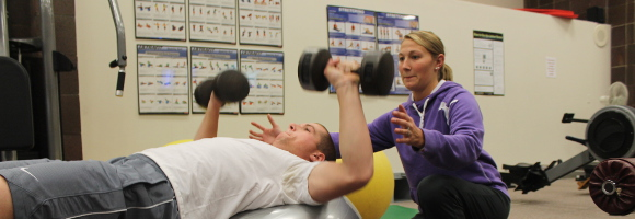 Female student spotting a male student who is lifting freeweights.
