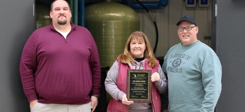 Pictured from left in front of the Devier Student Suites water pump house posing with the award are: Aaron Davenport, principal and sr. project manager for Jones & Henry, and Michelle Thibideau, GOCC water treatment operator and Larry Diekman GOCC maintenance manager.