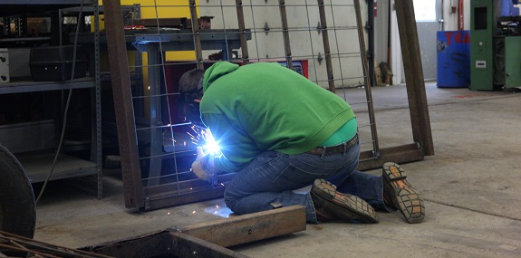 Student welding a steel frame.